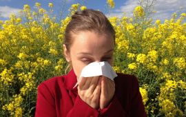 Woman with allergies in field of flowers blowing her nose