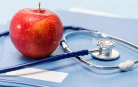Red apple and doctor's stethoscope lie on books.