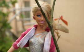 Barbie doll in the garden wearing pink sweatshirt.