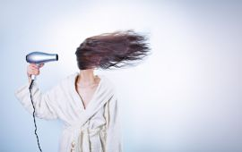 woman blow drying hair with hair covering face
