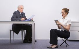 Boss sits at desk while secretary squishes down on low chair