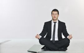 Man in business suit sitting in yoga lotus position with laptop computer.