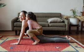 A mom doing yoga in the living room with daughter on her back