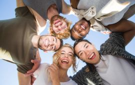 Teens gathered in circle looking down at camera