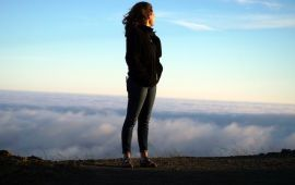 woman looking over cloud filled valley