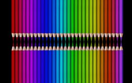 Rainbow array of colored pencils pointed toward each other