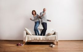 Couple standing on couch dancing