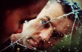 man looking at reflection in cracked wet mirror.