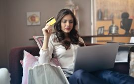 Woman with laptop holding credit card.