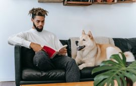 Man sits reading on his couch with dog at his side.