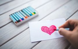 Hand holding red pastel drawing a heart on paper.