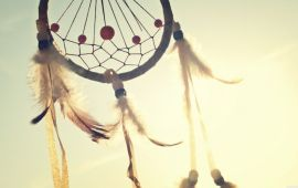 feathered dream catcher with sun behind