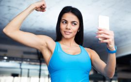 Fit woman posing for selfie while flexing muscle.
