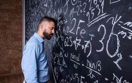 Exhausted man leans his head against blackboard in classroom