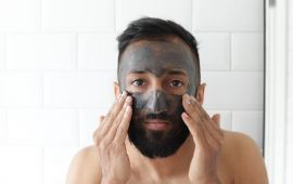 Man applying facial scrub in bathroom
