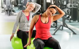Older woman and younger woman stretching on fitness balls at gym.