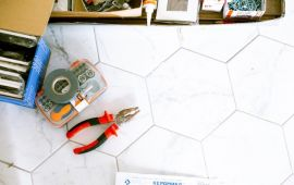 Home repair tools spread on a white tile floor
