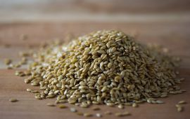 Pile of golden flax seed on wooden cutting board.