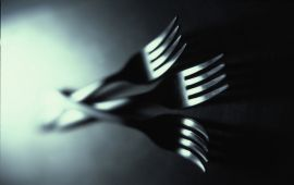 Black and white shot of three silver forks intertwined.