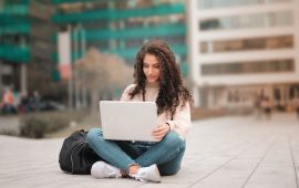Woman with laptop sitting on ground on college campus
