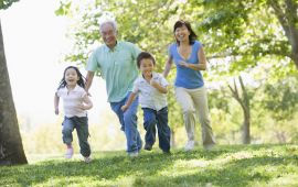 Grandfather running in park with family.