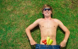 Shirtless man with sunglasses lying on grass with vegetables on his stomach