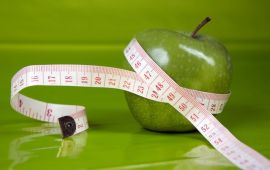 green apple on bright green background, wrapped in tape measure