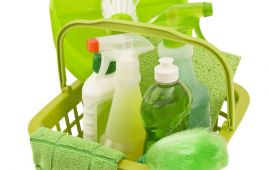 Basket of green colored cleaning supplies and items
