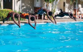 Four men dive from the side into a swimming pool.