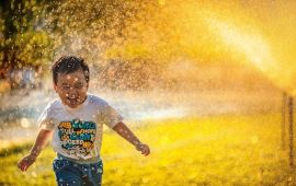 Laughing child running through sprinklers