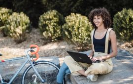 Woman sitting on rock outside while working on laptop computer