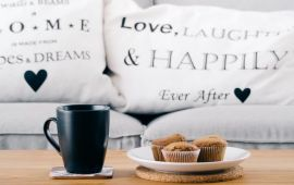 couch cushions say HOME and HAPPy with coffee and cookies
