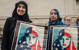 Two women in hijab holding up posters of women.