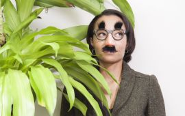 Woman in funny glasses and mustache hiding behind plant