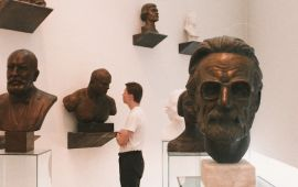 Young man looks at statue busts in museum