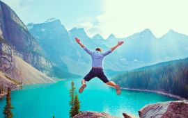 Man in mountain lake landscape jumping into the air
