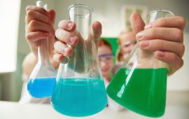 Kids holding up laboratory flasks with colored liquids.