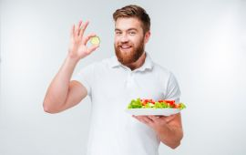 Bearded man in white shirt holding up vegetables from salad.