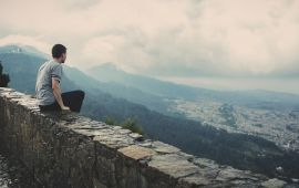 man on wall enjoying long view of city below