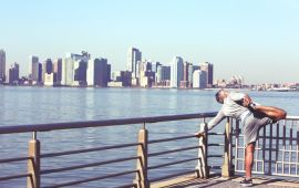 man in exercise clothes stretching at railing of waterfront with city skyline behind