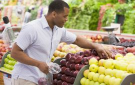 Man shopping for apples in produce aisle of grocery store.