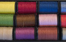 several spools of thread in various colors laid end-to-end