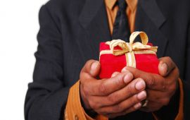 hands hold out a wrapped gift in offering