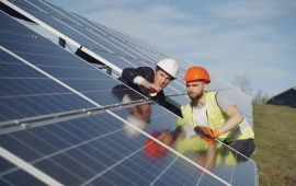 Two men in hardhats inspect solar panels