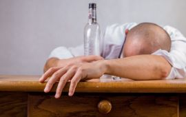 man passed out asleep on desk with alcohol bottle