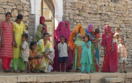 women and children of Rajasthan standing on stone wall