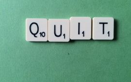 Scrabble tiles on green felt spell QUIT