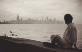 sepia photo of man sitting on stone wall looking across river at cityscape