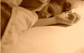 sepia-toned image of woman sleeping soundly on pillows in bed