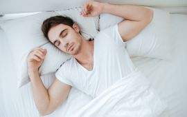 Man in white t shirt sleeping in white sheets.